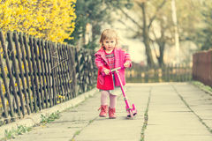 Year-old girl riding her scooter Stock Image