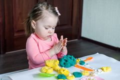 A 1.5 year old girl sits at a table and plays with a color test, on the table lie tools, molds and pasta for decor. royalty free stock photo