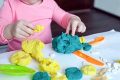 A 1.5 year old girl sits at a table and plays with a color test, on the table lie tools, molds and pasta for decor. stock image