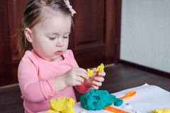 A 1.5 year old girl sits at a table and plays with a color test, on the table lie tools, molds and pasta for decor. A 1.5 year old girl sits at a table and royalty free stock photos