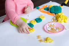A 1.5 year old girl sits at a table and plays with a color test, on the table lie tools, molds and pasta for decor. A 1.5 year old girl sits at a table and royalty free stock image