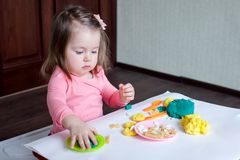 A 1.5 year old girl sits at a table and plays with a color test, on the table lie tools, molds and pasta for decor. A 1.5 year old girl sits at a table and stock photo