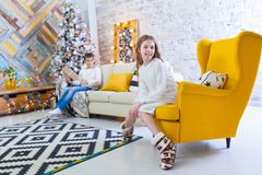 A 10-year-old girl sits on a yellow chair in the house before the Christmas holidays. In the background a boy is sitting Royalty Free Stock Images