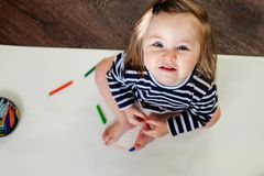 1 year old girl sitting on the floor with pencils and paper, looking at the camera. 1 year old girl sitting on the floor with pencils and paper, looking at the Royalty Free Stock Images