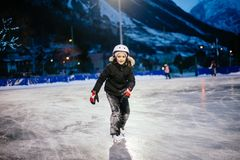 9 year old girl skates on the ice in the evening on an illuminat Stock Photos