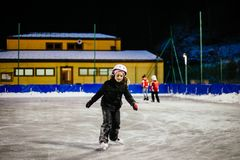 9 year old girl skates on the ice in the evening on an illuminat Royalty Free Stock Image