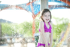 6 Year old girl at a splash park. Six year old girl enjoying summer by playing in the water at a splash park Royalty Free Stock Photos