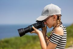 12 year old girl taking pictures in a beautiful scenic of Irish cliffs royalty free stock images