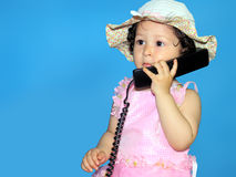 Two year old girl talking on the telephone. Isolated on blue Royalty Free Stock Images