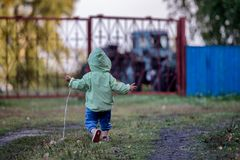 A kid is running on the grass in autumn. A 1,5 year old kid in a coat with a hood  is running on the grass towards a tractor parked outside the metal fence. Kid` Royalty Free Stock Image