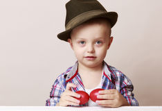 4 year old little and cute boy in a hat and shirt holding hands Stock Photo