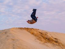 35-year-old man makes a somersault over a desert dune. 35-year-old man performs a somersault over a dune of the sahara desert at sunset, Douz Tunisia Royalty Free Stock Image
