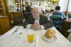 100 year old man sits down to a mug of beer and a loaf of bread in a restaurant in Madrid, Spain royalty free stock image