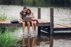A 13-year-old sister and her 11-year-old sister sit Teach homework with a computer with an internet on a wooden bridge, The river. Behind the house happily royalty free stock images