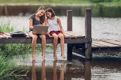 A 13-year-old sister and her 11-year-old sister sit Teach homework with a computer with an internet on a wooden bridge, The river. Behind the house happily royalty free stock photo