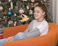 13-year old sitting in an orange chair smiling. Sideview of a smiling 13-year old with braces sitting in an orange chair in front of a Christmas tree stock image