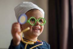 2 year old smiling boy playing doctor. Wearing toy medical equipment stock images