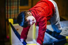 6-year-old child plays on the sunbed in his mountain house with. 6 year old smiling child plays on the sunbed in his mountain house with wooden walls Stock Image