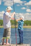 7-year-old son helps his father to fish. In the lake royalty free stock image