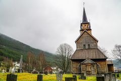 Stave church amidst graveyard in Norway on snowy day stock image