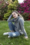 16 year old teenager sitting in a park with grass and flowers. Royalty Free Stock Photo