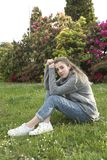 16 year old teenager sitting in a park with grass and flowers. Stock Photos