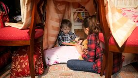 Cute 1 year old toddler boy reading book with elder sister in tent at bedroom. 1 year old toddler boy reading book with elder sister in tent at bedroom Stock Images