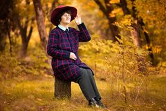 60 year old woman in red hat dreams in gold autumn park. Harmony royalty free stock images