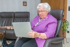Old woman is typing on a laptop royalty free stock photo