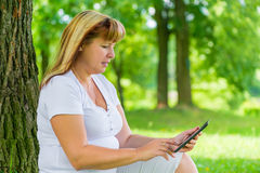 50 year old woman with a tablet in the park Royalty Free Stock Photography