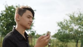 15 year old The young man makes a video call in nature. The guy in the hearing aids is talking on video with the help of. A smartphone stock footage