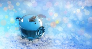 The year of the pig glass pig on the snow and the festive blue blurred bokeh background. Close-up royalty free stock image