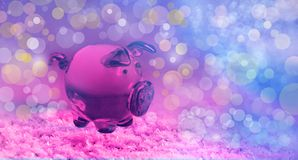 Year of pig glass piggy on snow and pink purple blurred festive bokeh background. Close-up royalty free stock photography