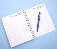 Year planner. Calendar with pen - year planner - isolated on blue Royalty Free Stock Photography