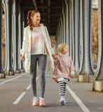 Active mother and child on Pont de Bir-Hakeim bridge walking Stock Image