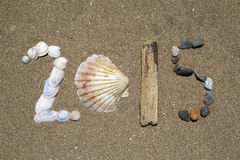 Year 2015. Shapes made of shells, drift wood and stones on the sand background Stock Photos