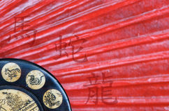 Year of the Snake. Antique Chinese Zodiac Wheel made of engraved bone and wood on red fan background; the wheel shows the horoscope year signs Snake, Dragon and royalty free stock photography