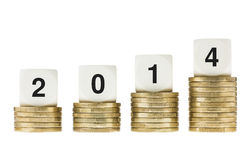 Year 2014 on Stacks of Gold Coins with White Background. Business, banking, investment and finance concept. Stacks of gold coins showing growth and increase Stock Photos