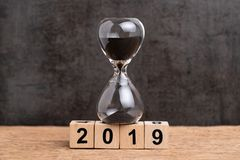 Year 2019 time countdown or time passing concept, hourglass or sandglass on cube wooden block building number 2019 on wood table royalty free stock photo