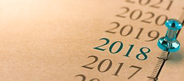 Year 2018, Two Thousand Eighteen on a timeline. 3D illustration of a timeline on kraft paper with focus on year 2018 and a blue thumbtack Royalty Free Stock Photography