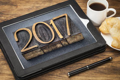 Year 2017 in vintage wood type on tablet. 2017 - New Year concept - number in vintage wood type printing blocks on a digital tablet with a cup of coffee and royalty free stock image