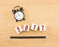2017 year on wood cube with pencil and clock top view on wood ta Royalty Free Stock Photography