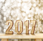 2017 year wood number on wood table with gold sparkling bokeh wa Royalty Free Stock Photography