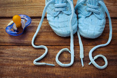 2016 year written laces of children's shoes and a pacifier Royalty Free Stock Photo