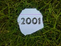 Year 2001 written on the piece of paper in the grass. Year 2001 written piece paper grass font text stock photography