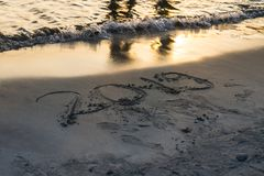 Year 2019 written on sand at sunset royalty free stock image