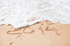 Year 2014 written in sand on tropical beach Stock Photos