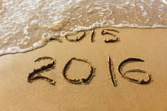 2015 and 2016 year written on sandy beach sea. Wave washes away 2015. Stock Photos