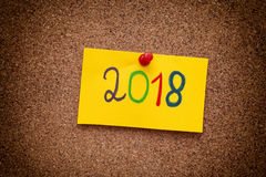 2018 year written on yellow paper note on cork board. Vignette. Close up Royalty Free Stock Images
