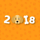 The year 2018 is a yellow earth dog. A lovely cartoon dog looks. Cartoon figures. Orange pattern from the tracks. Cover for the ca. Happy New Year. The year 2018 Stock Photography